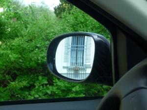 Окно дома в зеркале заднего вида